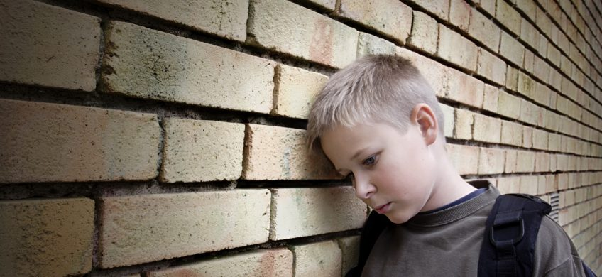 Sad bullied boy leaning on a wall